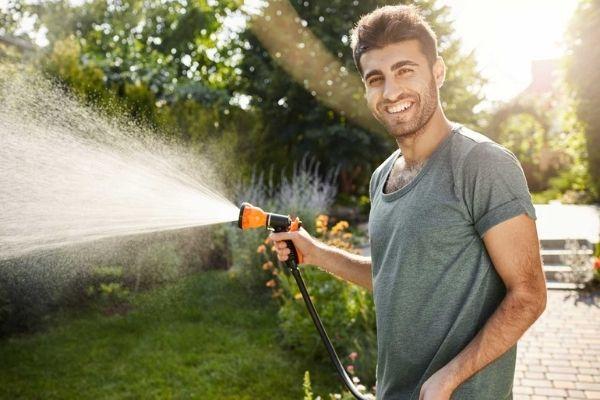 gardener smiling watering plants